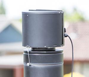 Draftbooster v čiernom vyhotovení nainštalovaný na komíne.